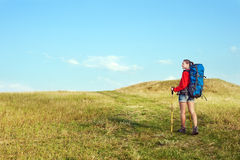 Hiking young woman with backpack and trekking poles Stock Photography