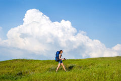 Hiking young woman with backpack and trekking poles walking. Smiling hiking young woman with backpack and trekking poles walking in a green meadow royalty free stock photos