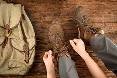 Hiking. Young woman is putting on shoes for hiking on wooden floor Royalty Free Stock Photos