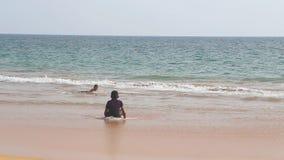 HIKKADUWA,斯里兰卡- 2014年2月:Hikkaduwa海滩看法,当波浪飞溅时和孩子在海洋享用 Hikkad 股票录像