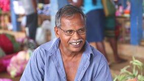 HIKKADUWA, ΣΡΙ ΛΑΝΚΑ - ΤΟ ΜΆΡΤΙΟ ΤΟΥ 2014: Πορτρέτο του τοπικού ηλικιωμένου χαμογελώντας ατόμου στην αγορά της Κυριακής Hikkaduwa απόθεμα βίντεο
