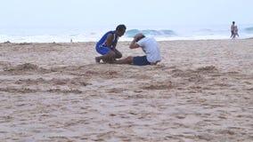 HIKKADUWA, ШРИ-ЛАНКА - МАРТ 2014: Взгляд 2 людей разрабатывая на пляже в Hikkaduwa Hikkaduwa известно для своего щеголя видеоматериал