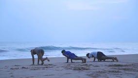 HIKKADUWA, ШРИ-ЛАНКА - МАРТ 2014: Взгляд 3 людей разрабатывая на пляже в Hikkaduwa Hikkaduwa известно для своего b сток-видео
