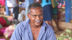 HIKKADUWA, ШРИ-ЛАНКА - МАРТ 2014: Портрет местного пожилого усмехаясь человека на рынке Hikkaduwa воскресенья, известный для свое сток-видео
