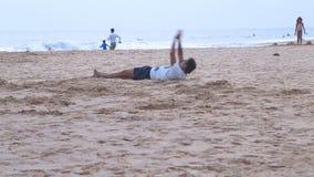 HIKKADUWA, ШРИ-ЛАНКА - МАРТ 2014: Человек разрабатывая на пляже в Hikkaduwa Hikkaduwa известно для своих красивых пляжей песка видеоматериал