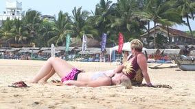 HIKKADUWA, ШРИ-ЛАНКА - ФЕВРАЛЬ 2014: Взгляд 2 женщин загорая на пляже Hikkaduwa Hikkaduwa известно для своего красивого пляжа видеоматериал