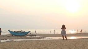 HIKKADUWA, ШРИ-ЛАНКА - ФЕВРАЛЬ 2014: Взгляд пляжа Hikkaduwa на заходе солнца пока люди идут на пляж Hikkaduwa известно сток-видео