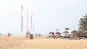 HIKKADUWA, ШРИ-ЛАНКА - ФЕВРАЛЬ 2014: Взгляд пляжа Hikkaduwa пока ветер дует в флагах на береге акции видеоматериалы