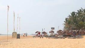 HIKKADUWA, ШРИ-ЛАНКА - ФЕВРАЛЬ 2014: Взгляд пляжа Hikkaduwa пока ветер дует в флагах на береге сток-видео