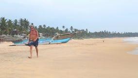 HIKKADUWA, ШРИ-ЛАНКА - ФЕВРАЛЬ 2014: Взгляд пляжа Hikkaduwa пока волны брызгают и человека проходит океаном Hikkadu акции видеоматериалы