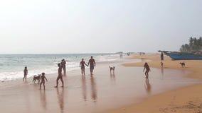 HIKKADUWA, ШРИ-ЛАНКА - ФЕВРАЛЬ 2014: Взгляд пляжа Hikkaduwa пока волны брызгают и люди наслаждаются около океана Высокий акции видеоматериалы