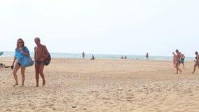 HIKKADUWA, ШРИ-ЛАНКА - ФЕВРАЛЬ 2014: Взгляд пляжа Hikkaduwa пока пары проходят Hikkaduwa известно для своего красивого beac акции видеоматериалы