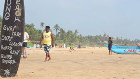 HIKKADUWA, ШРИ-ЛАНКА - ФЕВРАЛЬ 2014: Взгляд пляжа Hikkaduwa пока locals идут на пляж Hikkaduwa известно для своего b видеоматериал