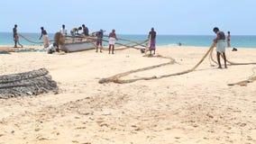 HIKKADUWA, ШРИ-ЛАНКА - ФЕВРАЛЬ 2014: Взгляд рыболовов работая на пляже Hikkaduwa Hikkaduwa известно для своего красивого beache сток-видео