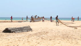 HIKKADUWA, ШРИ-ЛАНКА - ФЕВРАЛЬ 2014: Взгляд рыболовов работая на пляже Hikkaduwa Hikkaduwa известно для своего красивого beache видеоматериал