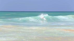 HIKKADUWA, ШРИ-ЛАНКА - ФЕВРАЛЬ 2014: Взгляд серфера занимаясь серфингом в океане на пляже Hikkaduwa Hikkaduwa известно для своего сток-видео