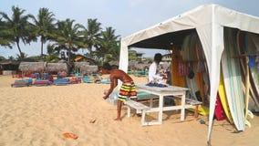 HIKKADUWA, ШРИ-ЛАНКА - ФЕВРАЛЬ 2014: Взгляд стойки прибоя и местного человека работая там на пляже Hikkaduwa Hikkaduwa известно д акции видеоматериалы