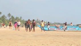 HIKKADUWA, ШРИ-ЛАНКА - ФЕВРАЛЬ 2014: Взгляд locals идя от шлюпки на пляже Hikkaduwa Hikkaduwa известно для своего красивого b видеоматериал