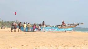 HIKKADUWA, ШРИ-ЛАНКА - ФЕВРАЛЬ 2014: Взгляд locals стоя и сидя на шлюпке на пляже Hikkaduwa Hikkaduwa известно для своего видеоматериал