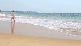 HIKKADUWA, ШРИ-ЛАНКА - ФЕВРАЛЬ 2014: Женщина выходя море на песчаном пляже в тропиках Hikkaduwa известно для своего красивого пля сток-видео
