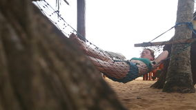 HIKKADUWA, ШРИ-ЛАНКА - ФЕВРАЛЬ 2014: Женщина спать в гамаке на пляже в Hikkaduwa Hikkaduwa известно для своего красивого b видеоматериал