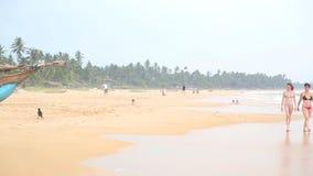 HIKKADUWA, ШРИ-ЛАНКА - ФЕВРАЛЬ 2014: Женщины и ребенок идя на пляж за шлюпкой Hikkaduwa известно для своих красивых пляжей сток-видео