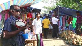 HIKKADUWA, ШРИ-ЛАНКА - ФЕВРАЛЬ 2014: Местный слепой поя пока люди проходят мимо на рынок Рынок i Hikkaduwa воскресенья акции видеоматериалы