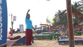 HIKKADUWA, ШРИ-ЛАНКА - ФЕВРАЛЬ 2014: Местный человек продавая драконов воздуха на пляже Hikkaduwa Hikkaduwa известно для своего к акции видеоматериалы