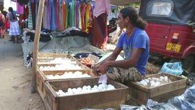 HIKKADUWA, ШРИ-ЛАНКА - ФЕВРАЛЬ 2014: Местный человек сидя и продавая на известном рынке Hikkaduwa воскресенья, для своего широког сток-видео