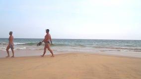 HIKKADUWA, ШРИ-ЛАНКА - ФЕВРАЛЬ 2014: Пожилые пары идя вдоль пляжа в их костюмах заплыва Hikkaduwa известно для своего beautifu видеоматериал