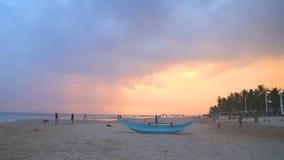HIKKADUWA, ШРИ-ЛАНКА - ФЕВРАЛЬ 2014: Традиционная рыбацкая лодка на пляже Hikkaduwa на заходе солнца Hikkaduwa известно для свое  акции видеоматериалы