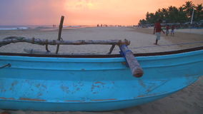 HIKKADUWA, ШРИ-ЛАНКА - ФЕВРАЛЬ 2014: Традиционная рыбацкая лодка на пляже Hikkaduwa на заходе солнца Hikkaduwa известно для свое  сток-видео