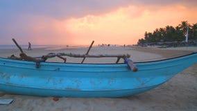 HIKKADUWA, ШРИ-ЛАНКА - ФЕВРАЛЬ 2014: Традиционная рыбацкая лодка на пляже Hikkaduwa на заходе солнца Hikkaduwa известно для свое  видеоматериал