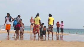 HIKKADUWA, ШРИ-ЛАНКА - ФЕВРАЛЬ 2014: Locals наслаждаясь пляжем и играя в прибое Волны очень сильны и не много locals сток-видео