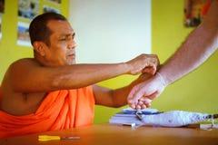 Hikkaduwa, Sri Lanka - 31 de enero de 2017: Monje budista Binds un hilo blanco, una secuencia, un encanto a la mano Fotos de archivo