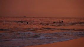 HIKKADUWA, SRI LANKA - EM FEVEREIRO DE 2014: A vista da praia de Hikkaduwa no por do sol, quando as ondas espirrarem e os povos e filme