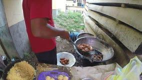 HIKKADUWA, SRI LANKA - EM MARÇO DE 2014: Equipe o cozimento do alimento no lado da rua O alimento da rua é muito comum, saboroso  video estoque