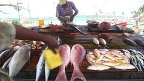 HIKKADUWA, SRI LANKA - EM MARÇO DE 2014: Peixes locais do corte do homem no mercado de Hikkaduwa domingo, conhecido para sua vast filme