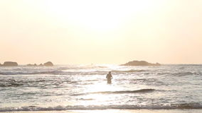 HIKKADUWA, SRI LANKA - FEBRERO DE 2014: Vista al mar en Hikkaduwa en puesta del sol con las ondas que salpican la playa y a la ge almacen de video