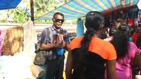 HIKKADUWA, SRI LANKA - FEBRUAR 2014: Ansicht des lokalen Blinders Tamburin an Hikkaduwa-Markt singend und spielend Hikkaduwa Sonn stock video footage