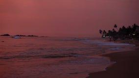 HIKKADUWA, SRI LANKA - FEBRUAR 2014: Ansicht von Hikkaduwa-Strand bei Sonnenuntergang, während Wellen spritzen Hikkaduwa ist für  stock footage
