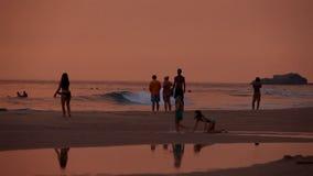 HIKKADUWA, SRI LANKA - FEBRUAR 2014: Ansicht von Hikkaduwa-Strand bei Sonnenuntergang, während Wellen spritzen und Leute spielen  stock footage