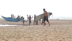 HIKKADUWA, SRI LANKA - FEBRUAR 2014: Ansicht von Hikkaduwa-Strand, während Kinder spielen und Leute gehen auf den Strand Hikkaduw stock video footage