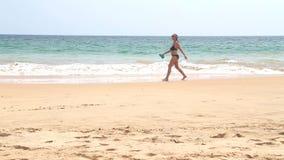HIKKADUWA, SRI LANKA - FEBRUAR 2014: Ansicht von Hikkaduwa-Strand, während Wellen spritzen und von Frau überschreitet durch den O stock footage