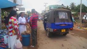 HIKKADUWA, SRI LANKA - FEBRUAR 2014: Die Ansicht der lokalen Straße nahe Markt und der Leute, die vorbei an Markt Hikkaduwa Sonnt stock footage