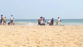 HIKKADUWA, SRI LANKA - FEBRUAR 2014: Einheimische, die den Strand genießen und in der Brandung spielen Wellen sind sehr stark und stock video footage