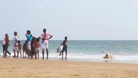 HIKKADUWA, SRI LANKA - FEBRUAR 2014: Einheimische, die den Strand genießen und in der Brandung spielen Wellen sind sehr stark und stock video