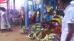 HIKKADUWA, SRI LANKA - FEBRUAR 2014: Einheimische, die ihr Erzeugnis an Markt Hikkaduwa Sonntag, bekannt für seine breite Palette stock video