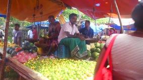HIKKADUWA, SRI LANKA - FEBRUAR 2014: Lokale Männer, die an Hikkaduwa-Markt sitzen und verkaufen Markt Hikkaduwa Sonntag bekannt f stock footage