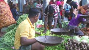 HIKKADUWA, SRI LANKA - FEBRUAR 2014: Lokale Männer, die an Markt Hikkaduwa Sonntag, bekannt für seine breite Palette von frischem stock footage